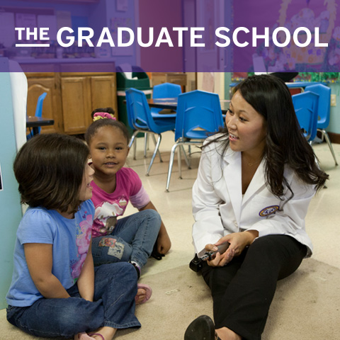 The Graduate School - A grad student sits on the floor of a classroom with two children
