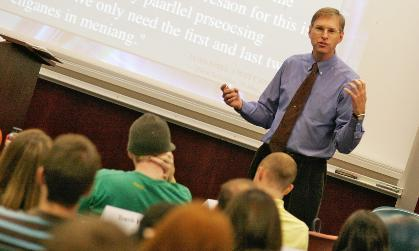 A College of Business faculty member interacts with his class