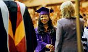 A JMU graduate in her purple and gold graduation robes.