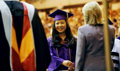 Smiling student in purple and gold graduation cap and gown receives degree