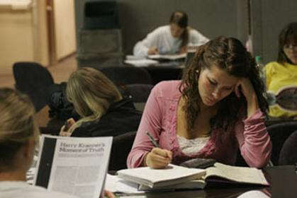 Female business student studying over books, surrounded by studying students in classroom