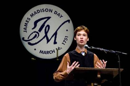 Male student speaks at podium with a sign reading James Madison Day, March 16 1751 in background