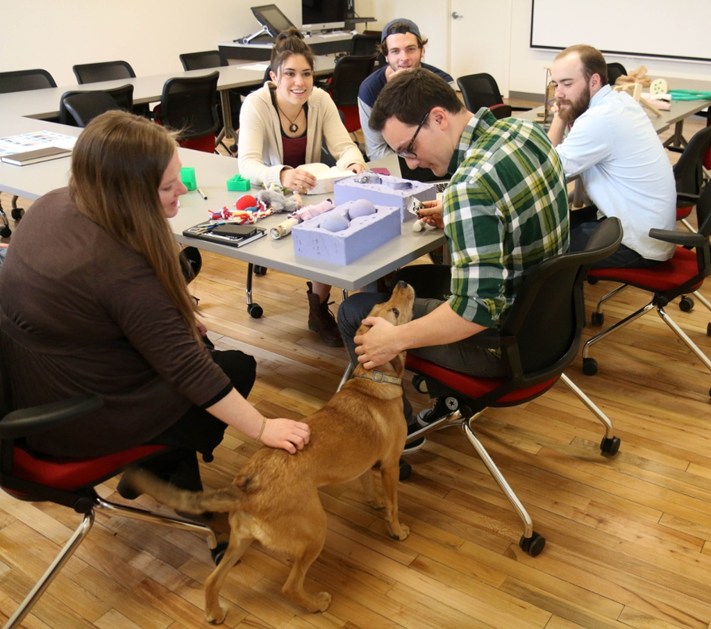 Pet product testing. Students and teacher with dog at table.