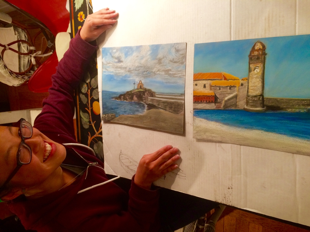 Stephanie Chong with her two pastels of the harbor in Collioure, France