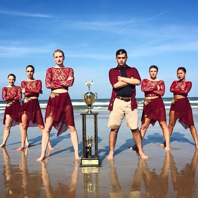 The Dukettes take a photo next to their trophy