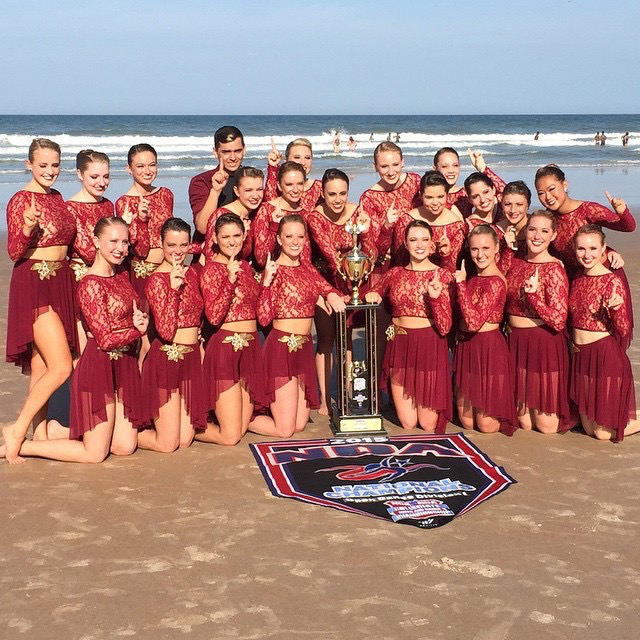 The JMU Dukettes pose on the beach after their win