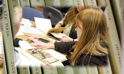 Students do hands-on research in JMU's collection of Black Mask magazines