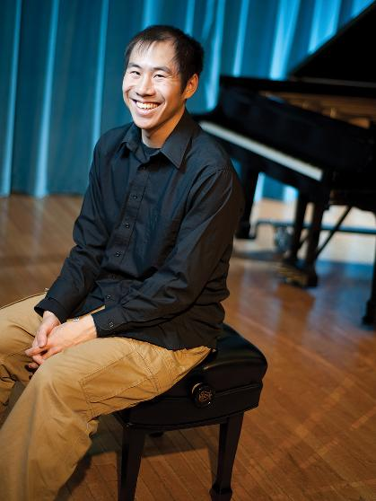 Andrew Pham sits on a piano bench and smiles while on stage.