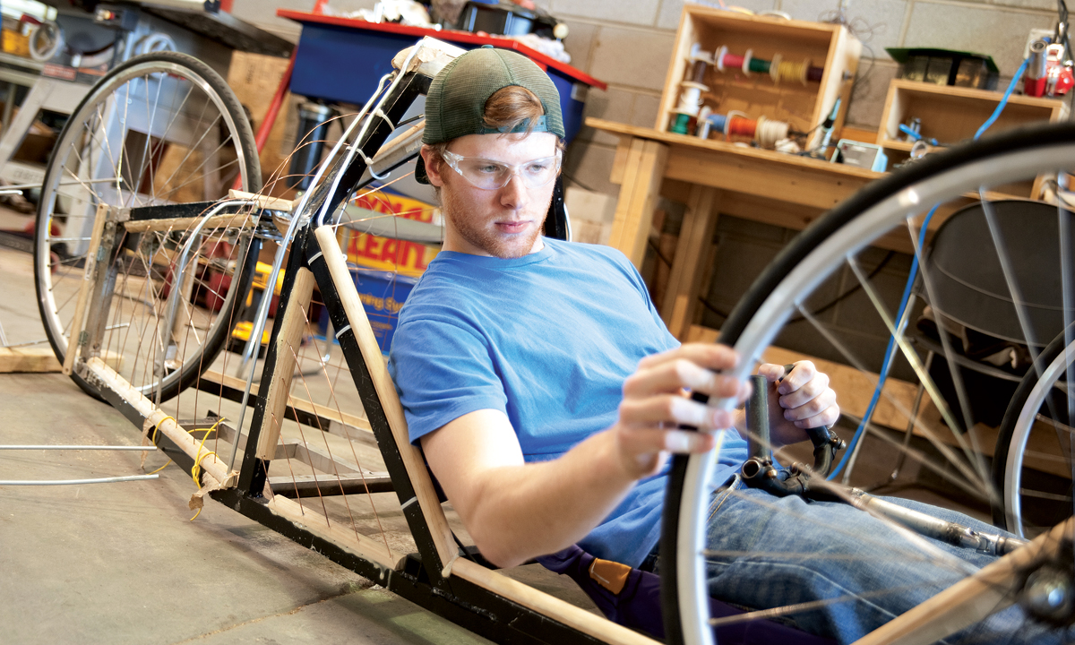 J.T. Danko ('10) checks the wheel on the supermileage vehicle he helped build in the JMU Alternative Fuels Lab.