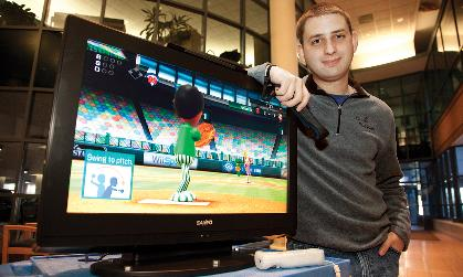 Mike Miriello ('09M) leans on a TV that is hooked up to a Wii video game.