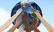 Diverse hands reaching toward the globe, together