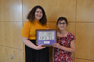 JMU Student Lydia Manson presents the award for best currency design, and award she, herself won as a middle school student
