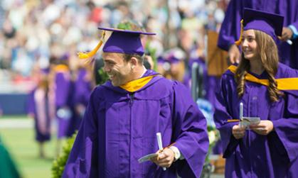 New JMU graduates exiting the stage after receiving degrees