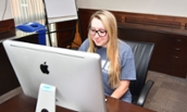 QFIN major Heather Caminske sitting at an iMac