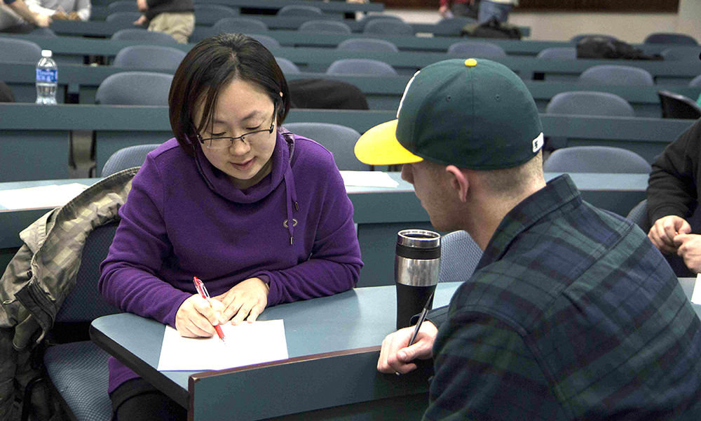 Dr. Hui He Sono consulting with a student in a lecture hall - 2017