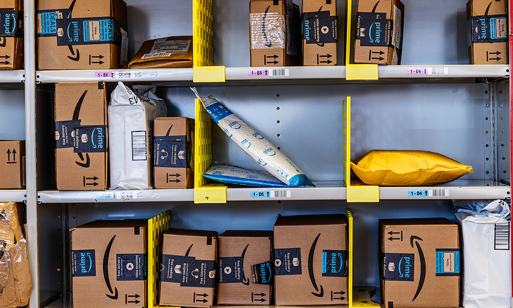Warehouse shelves full of packages at an Amazon Fulfillment Center (by Jonathan Weiss)