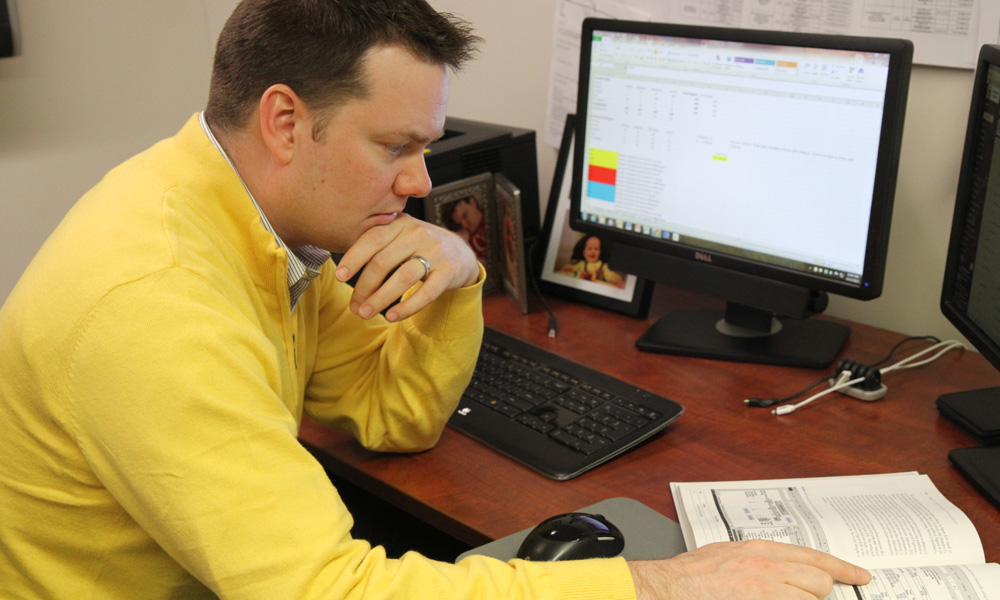 MBA Student in yellow sweater studying at a desk with book and computer