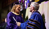 Graduate student receiving diploma from President Alger at 2018 winter commencement