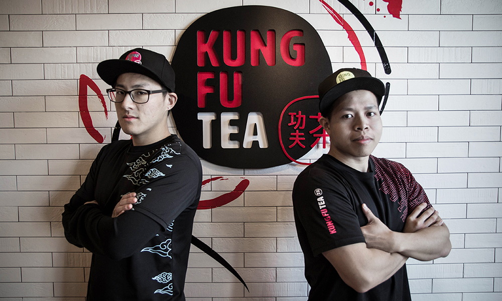 Michael Wu and Parter posing in front of the Kung Fu Tea logo