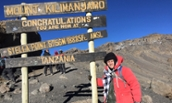 Matthew Fracasso standing by Mt. Kilimanjaro sign - 2016