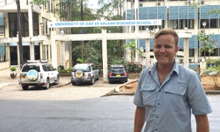 Matthew Fracasso in Tanzania in front of the local Business School