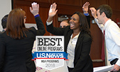 MBA Students high fiving at a workshop - 2016 - with US News 2018 Badge