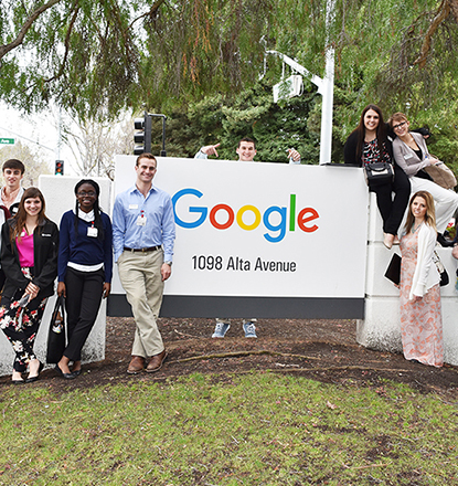 Students posing around Google headquarters sign