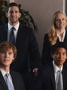 4 CoB students in suits, in a conference room