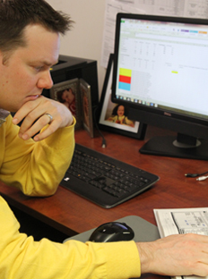 MBA student in yellow sweater working at a computer