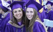 Two female students in cap and gown at CoB Graduation May 2015