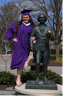 picture of tutor Becky Rosen in graduation gear next to James Madison statue
