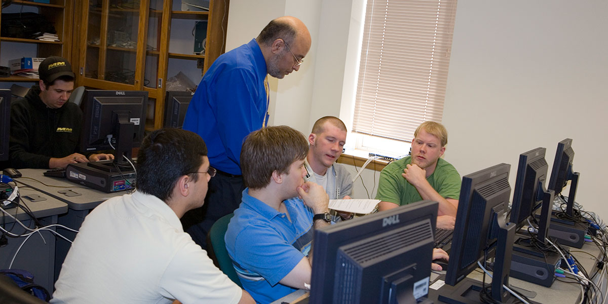 A Compute Science professor instructs students in a lab