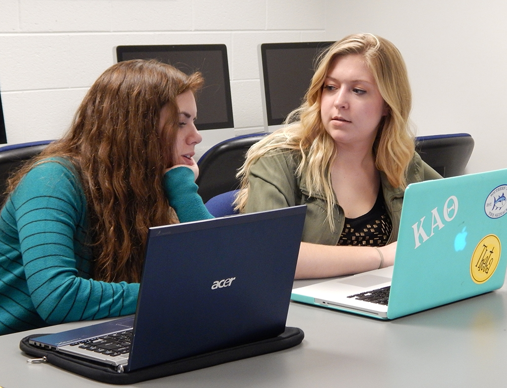 Image of two students working together with laptops.