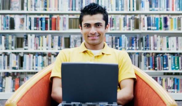 Student in a library with a laptop