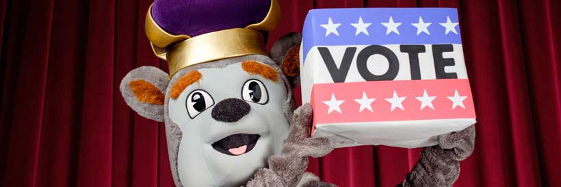Duke Dog holds up a red, white and blue ballot box.