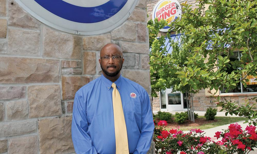 Gilbert Bland standing in front of a Burger King restaurant.