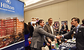 Representatives from Hilton talking with a student at the Fall Career Fair - 2019