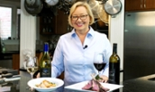 Tassie Pippert in kitchen with wine and lamb chops - 2018