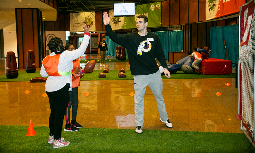Hart School volunteer high-fiving a student during Qatar National Sports Day - 2019