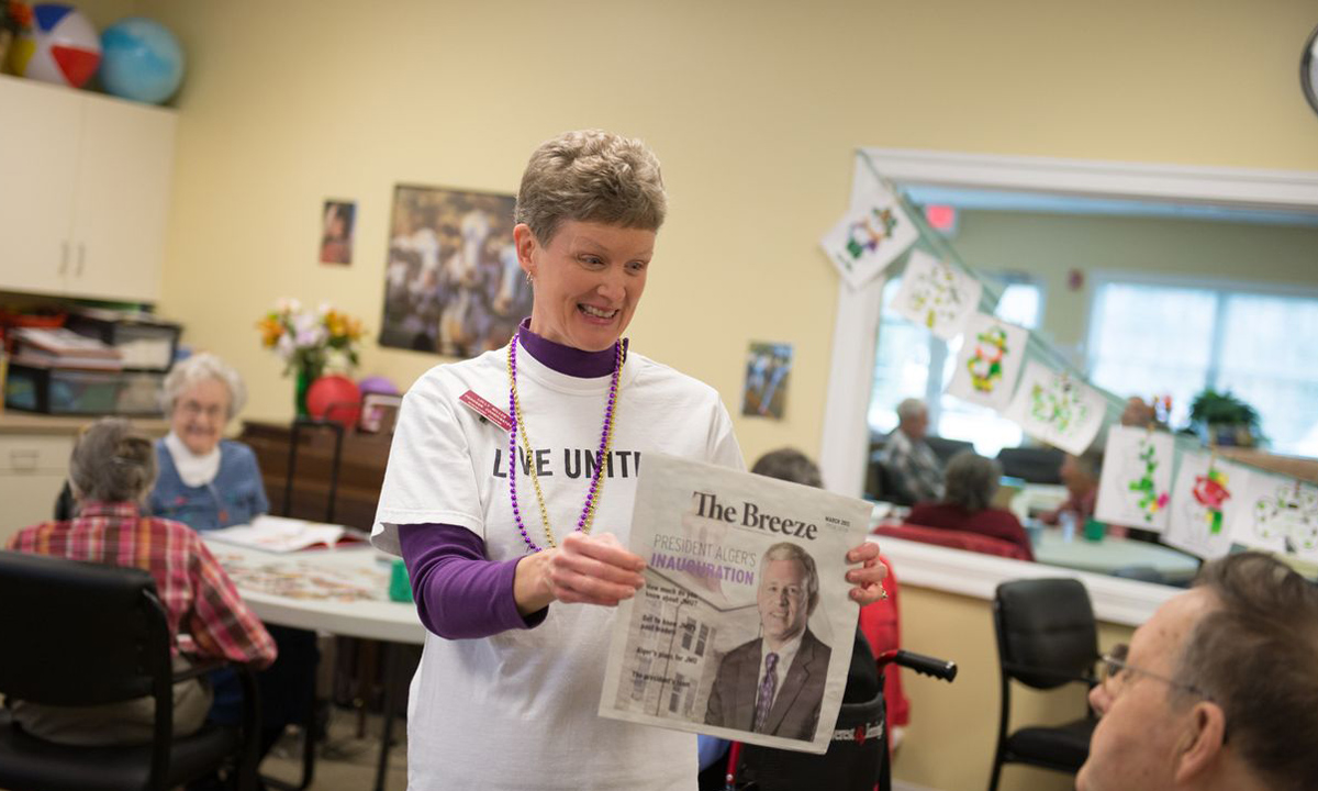 "Generations Crossing director of adult programs, Lolley Miller, holds up a copy of the Breeze during a JMU Trivia game. One of the participants yelled out ""He's nice looking!"""