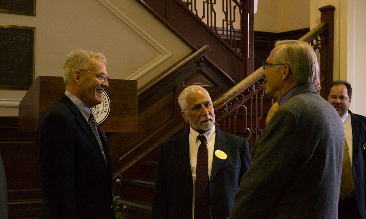 Professor Emeritus of Communication and JMU Faculty Emeriti Association President Rex Fuller and Dean of Libraries and Educational Technologies Ralph Alberico (center) talk with faculty emeriti members at the reception.