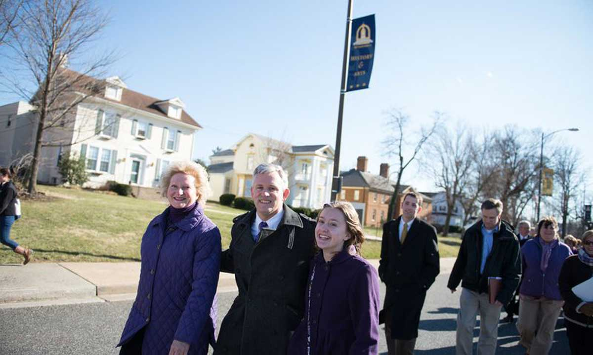 The Alger family, Jon, Mary Ann and daughter Eleanor, lead the ceremonial walk from campus to Harrisonburg's Court Square followed by approximately 200 students, faculty, staff and community members.