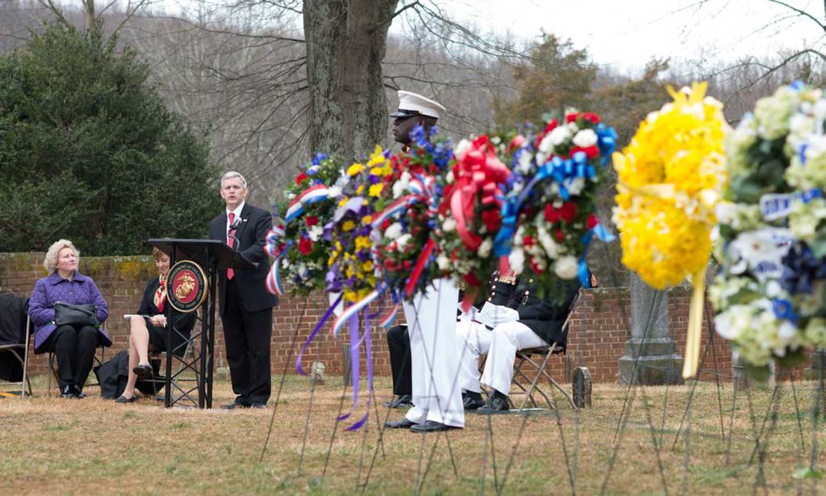 JMU president Jon Alger speaks amid a collection of wreaths to commemorate the 262nd anniversary of the birth of James Madison on Saturday at Montpelier.