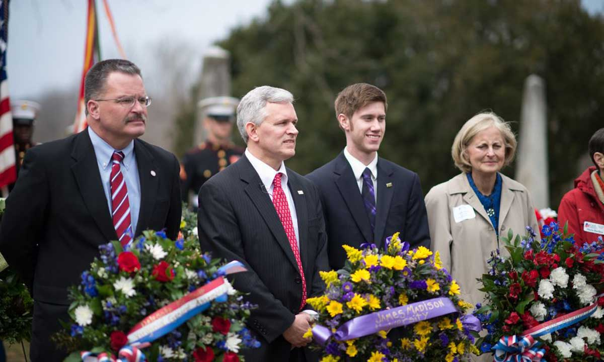 President Alger, second from left, stands behind a purple and gold wreath to be laid at President James Madison's tomb.