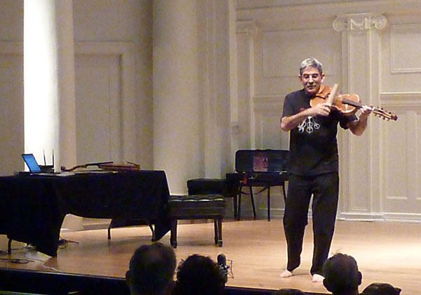 Stephen Nachmanovitch laying violin on a stage