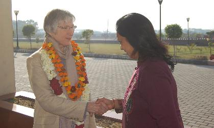 Dr. Louise Temple wears a colorful lay as she shakes hands with a representative of the university in India.
