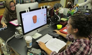 Student Leah Schaller facing a computer screen displaying her project design on the screen - a brown cylander in the center and, off to the right side, icons for the software tools.