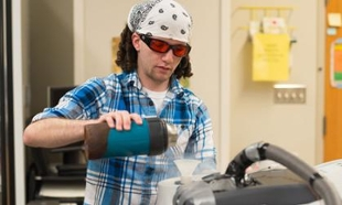 student wearing lab glasses pours liquid into a machine in the lab.