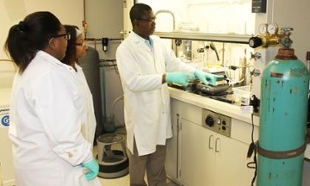 Dr. Debo Ogunjirin works with two students in a chemistry lab. All are wearing white lab coats and looking at a bench that has a glass cover over the top part of it.