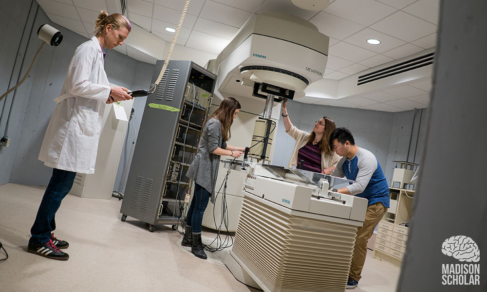 Four people in the lab, one standing off to the left of the acclerator machine wearing a white lab coat and holding a clipboard; and the other three wokring around the large machine.
